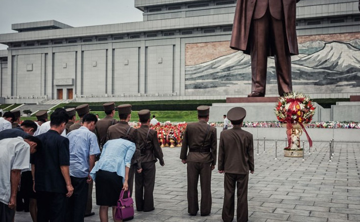 north Koreans bowing down to statue